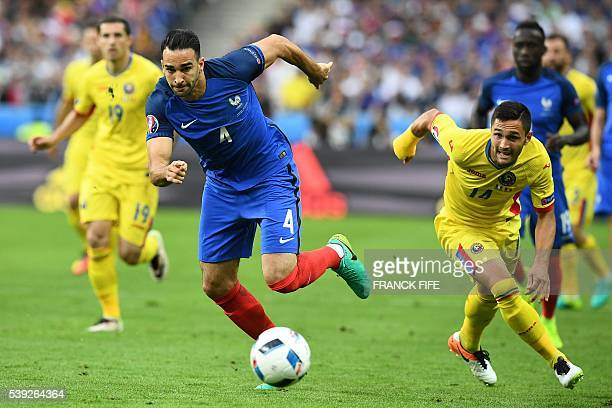 France's defender Adil Rami and Romania's forward Florin Andone vie for the ball during the Euro 2016 group A football match between France and...