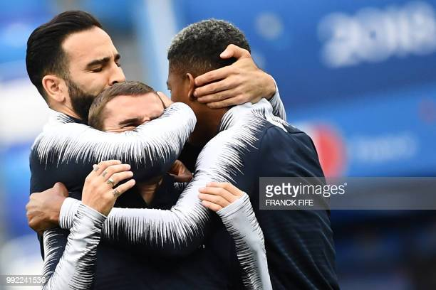 France's defender Adil Rami France's forward Antoine Griezmann and France's defender Presnel Kimpembe joke together as they take part in a training...