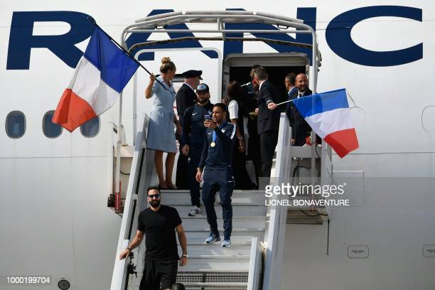 France's defender Adil Rami France's midfielder Corentin Tolisso and France's midfielder Nabil Fekir disembark from the plane upon their arrival at...