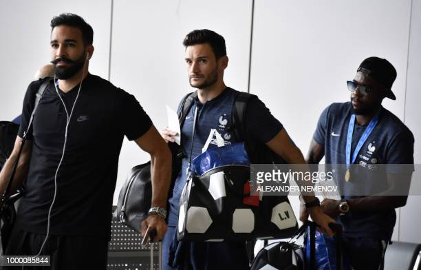 France's defender Adil Rami goalkeeper Hugo Lloris and defender Samuel Umtiti depart home from Moscow's Sheremetyevo airport on July 16 after winning...