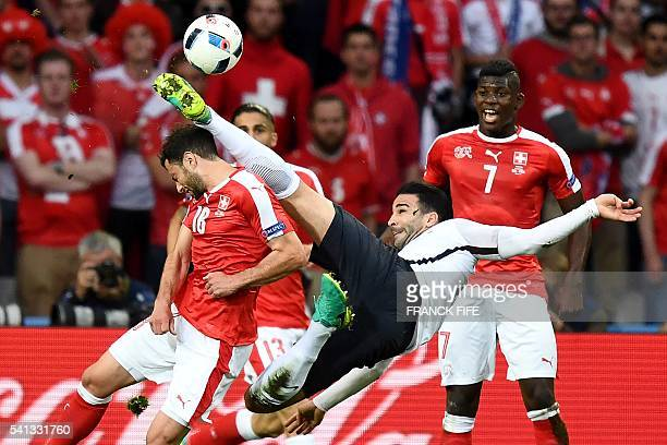 TOPSHOT France's defender Adil Rami kicks the ball over Switzerland's forward Admir Mehmedi during the Euro 2016 group A football match between...