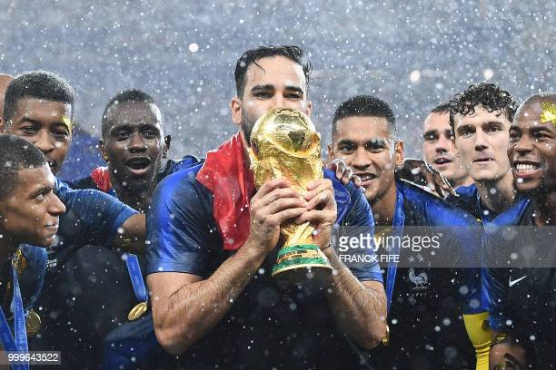 France's defender Adil Rami kisses their World Cup trophy as they celebrate their win at the end of the Russia 2018 World Cup final football match...