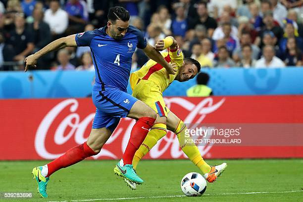France's defender Adil Rami vies for the ball with Romania's forward Florin Andone during the Euro 2016 group A football match between France and...