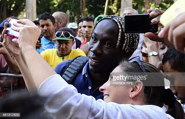 France's defender Bacary Sagna poses with a brazilian fans as he arrives for a press conference at the theater in Ribeirao Preto on June 27 during...