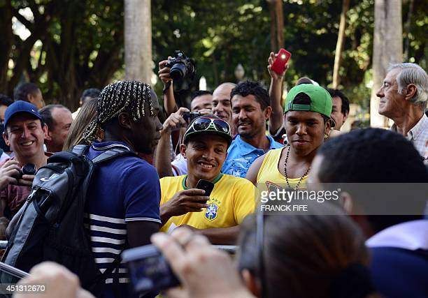 France's defender Bacary Sagna poses with Brazilian fans as he arrives for a press conference at the theater in Ribeirao Preto on June 27 during the...
