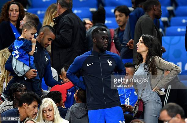 France's defender Bacary Sagna speaks with his wife Ludivine Sagna following the Euro 2016 quarterfinal football match between France and Iceland at...