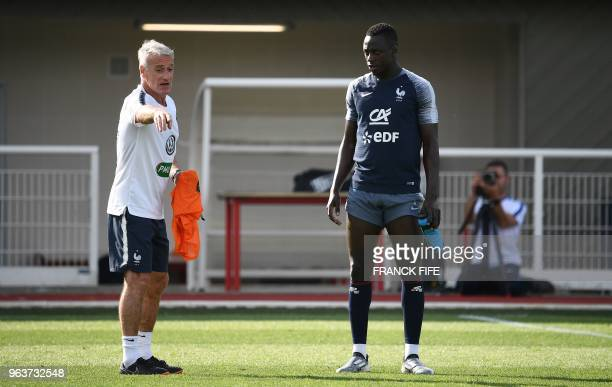 France's defender Benjamin Mendy speaks with France's head coach Didier Deschamps during a training session in Clairefontaine en Yvelines on May 30...