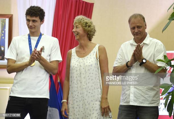 France's defender Benjamin Pavard flanked by his parents Nathalie and Frederic applauds at the townhall in his home town of Jeumont northern France...