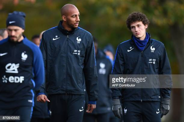 France's defender Benjamin Pavard speaks with France's midfielder Steven N'zonzi prior to a training session in Clairefontaine-en-Yvelines near Paris...