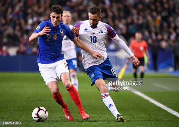 France's defender Benjamin Pavard vies for the ball with Iceland's midfielder Gylfi Sigurdsson during the UEFA Euro 2020 Group H qualification...