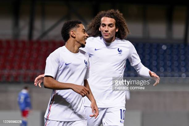 France's defender Colin Dagba celebrates after scoring his team's first goal with France's midfielder Matteo Guendouzi during the 2021 U21 European...