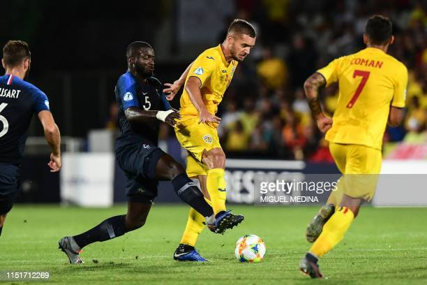 France's defender Dayot Upamecano tackles Romania's forward George Puscas during the Group C match of the U21 European Football Championships between...