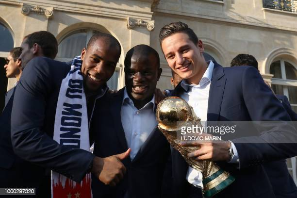 France's defender Djibril Sidibe France's midfielder N'Golo Kante and France's forward Florian Thauvin pose for a photograph in the grounds of the...