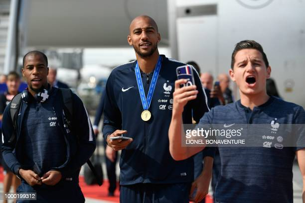France's defender Djibril Sidibe France's midfielder Steven N'Zonzi and France's forward Florian Thauvin celebrate after disembarking from the plane...