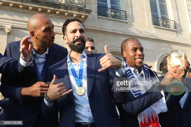 France's defender Djibril Sidibe holds the winner's trophy as France's midfielder Steven N'Zonzi speaks with defender Adil Rami and during an...