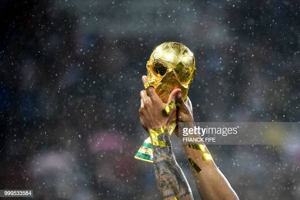 TOPSHOT France's defender Djibril Sidibe raises their World Cup trophy during the trophy ceremony at the end of the Russia 2018 World Cup final...