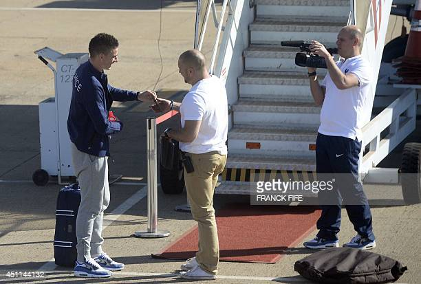 France's defender Laurent Koscielny boards a plane at the airport in Ribeirao Preto on June 25 on the eve of a Group E football match between France...