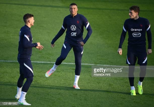 France's defender Lucas Hernandez, France's forward Kylian Mbappe and France's defender Benjamin Pavard warm up during a training session in...