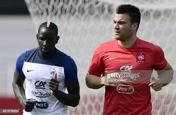 France's defender Mamadou Sakho runs with a staff member during a training session at the stadium Santa Cruz in Ribeirao Preto on June 28 during the...