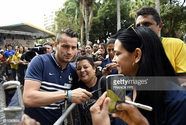 France's defender Mathieu Debuchy poses with a fan before a press conference at the theater in Ribeirao Preto on June 23, 2014 during the 2014 FIFA...