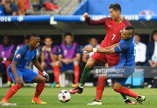 TOPSHOT France's defender Patrice Evra and France's forward Dimitri Payet vie with Portugal's forward Cristiano Ronaldo during the Euro 2016 final...