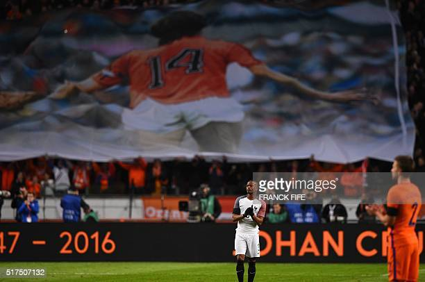 France's defender Patrice Evra applauds as a large banner is displayed during a standing ovation in honour of late Dutch football legend Johann...