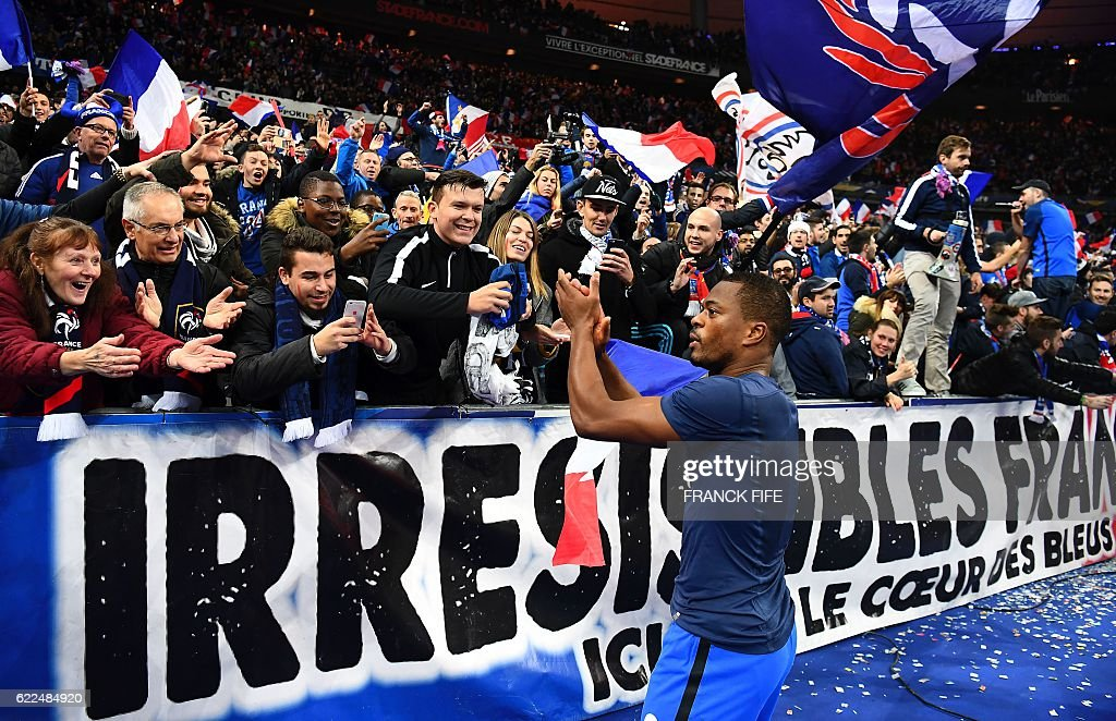 TOPSHOT - France's defender Patrice Evra celebrates with fans at the end of the 2018 World Cup group A qualifying football match between France and Sweden at the Stade de France in Saint-Denis, north of Paris, on November 11, 2016. / AFP / FRANCK