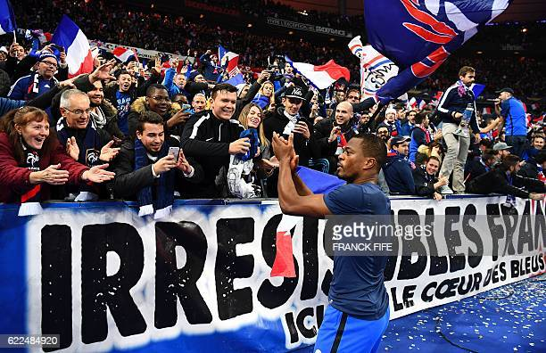 TOPSHOT France's defender Patrice Evra celebrates with fans at the end of the 2018 World Cup group A qualifying football match between France and...