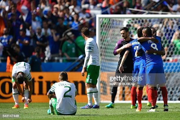 TOPSHOT France's defender Patrice Evra hugs France's forward Dimitri Payet after winning the Euro 2016 round of 16 football match between France and...