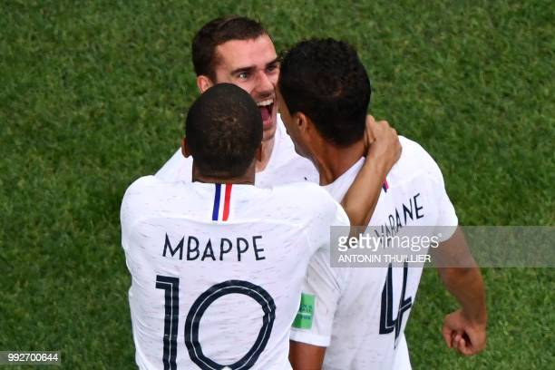 TOPSHOT France's defender Raphael Varane celebrates his goal with France's forward Antoine Griezmann and France's forward Kylian Mbappe during the...