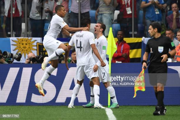 TOPSHOT France's defender Raphael Varane celebrates with France's forward Antoine Griezmann and France's forward Kylian Mbappe after scoring the...