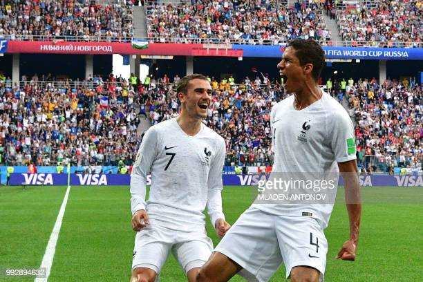 TOPSHOT France's defender Raphael Varane celebrates with France's forward Antoine Griezmann after scoring the opener during the Russia 2018 World Cup...