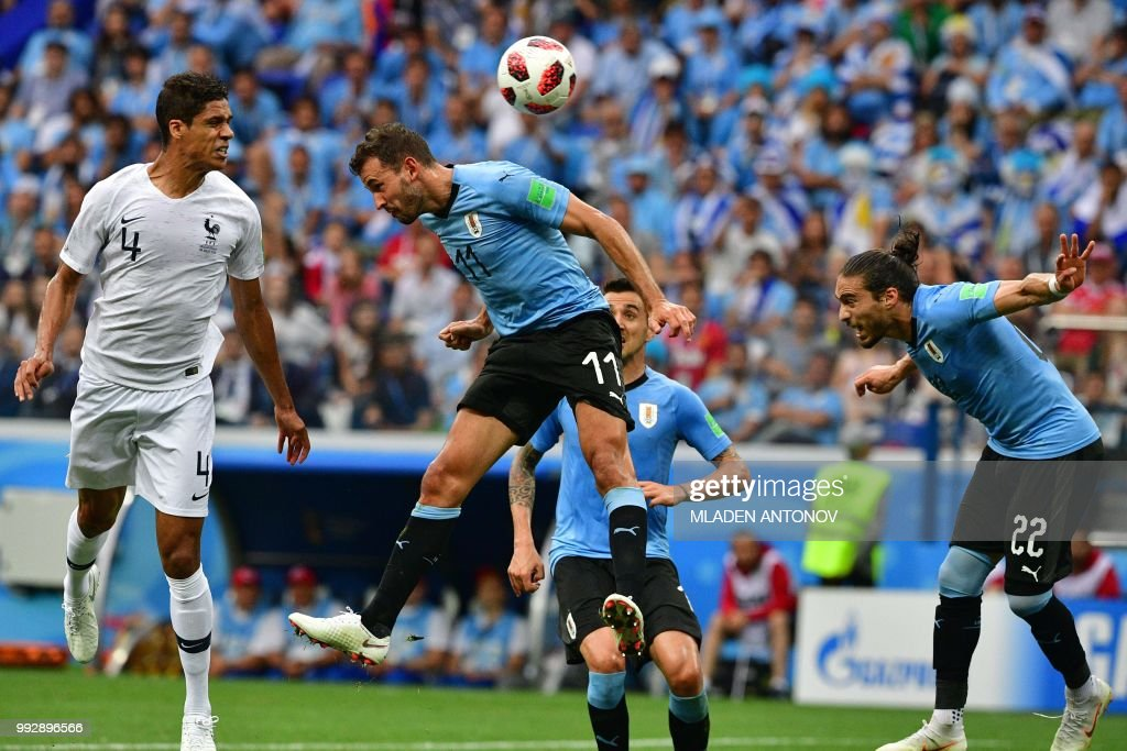 TOPSHOT - France's defender Raphael Varane (L) heads to score the opener past Uruguay's forward Cristhian Stuani (C) and Uruguay's defender Martin Caceres during the Russia 2018 World Cup quarter-final football match between Uruguay and France at the Nizhny Novgorod Stadium in Nizhny Novgorod on July 6, 2018.