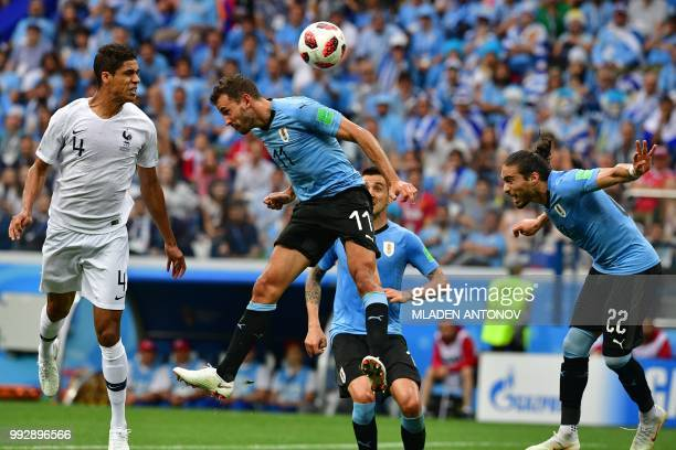 TOPSHOT France's defender Raphael Varane heads to score the opener past Uruguay's forward Cristhian Stuani and Uruguay's defender Martin Caceres...
