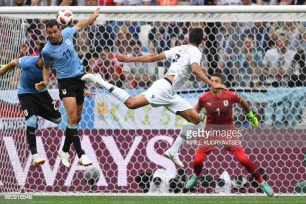 TOPSHOT France's defender Raphael Varane heads to score the opener past Uruguay's forward Cristhian Stuani during the Russia 2018 World Cup...