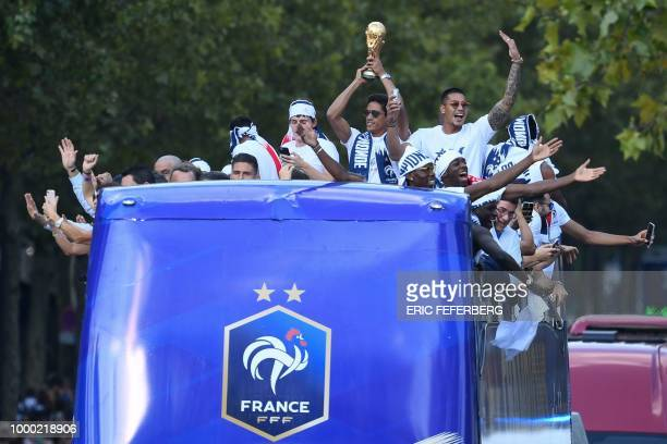 France's defender Raphael Varane holds the trophy as he celebrates with teammates on the roof of a bus while parading down the Champs-Elysee avenue...