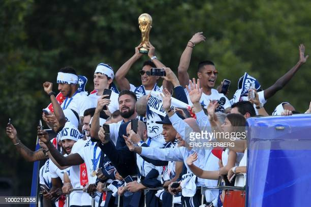 TOPSHOT France's defender Raphael Varane holds the trophy as he celebrates with teammates on the roof of a bus while parading down the ChampsElysee...
