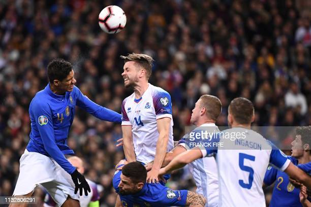 France's defender Raphael Varane vies for the ball with Iceland's defender Kari Arnason during the UEFA Euro 2020 Group H qualification football...