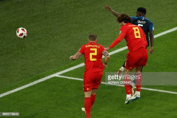 France's defender Samuel Umtiti heads the ball and scores next to Belgium's midfielder Marouane Fellaini and Belgium's defender Toby Alderweireld...