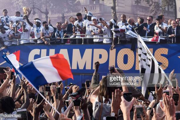 TOPSHOT France's defender Samuel Umtiti holds the trophy as he celebrates with teammates on the roof of a bus while parading down the ChampsElysee...