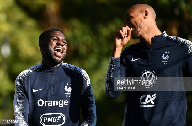 France's defender Samuel Umtiti shares a laugh with France's midfielder Steven N'zonzi during a training session at the French national football team...