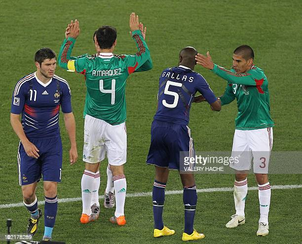 France's defender William Gallas shakes hands with Mexico's defender Carlos Salcido as Mexico's striker Javier Hernandez celebrates as France's...