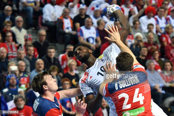 France's Dika Mem jumps to shoot between Norway's Sander Sagosen and Christian O'Sullivan during the preliminary round group B match of the Men's...