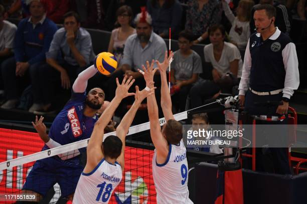 France's Earvin Ngapeth hits the ball against Serbia's Marko Podrascanin and Serbia's Nikola Jovovic during the semi final match of the men's 2019...