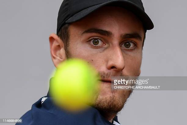 France's Elliot Benchetrit eyes the ball as he returns the ball to Britain's Cameron Norrie during their men's singles first round match on day three...
