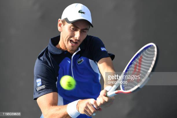 France's Elliot Benchetrit hits a return against Japan's Yuichi Sugita during their men's singles match on day two of the Australian Open tennis...