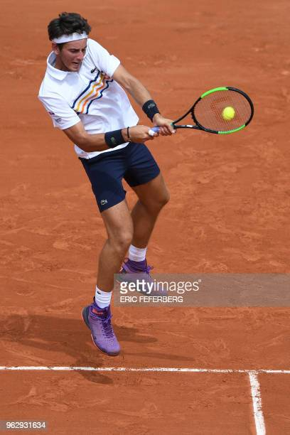 France's Elliot Benchetrit plays a backhand return to compatriot Gael Monfils during their men's singles first round match on day one of The Roland...