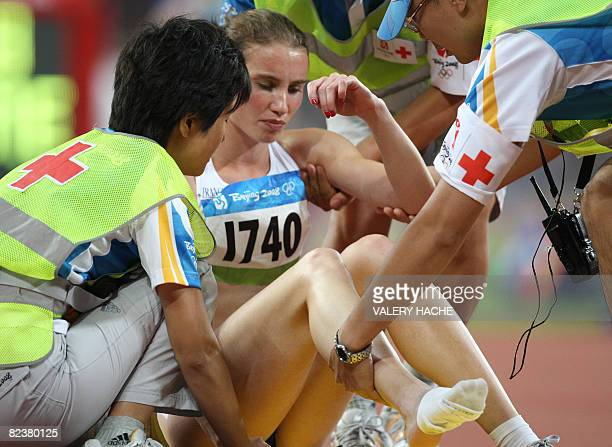 France's Elodie Guegan is placed on a stretcher after suffering an injury while competing in the women's 800m semifinal 3 at the 'Bird's Nest'...