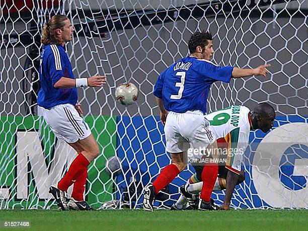 France's Emmanuel Petit and Bixente Lizarazu look on as Senegalese midfielder Pape Bouba Diop gets up after scoring the first goal of the 2002 FIFA...