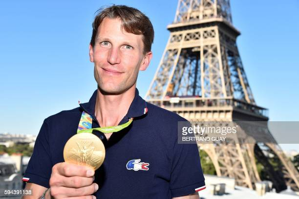 France's Equestrian Jumping team rider Kevin Staut poses with his gold medal on August 23 in front of the Eiffel tower in Paris. France's Olympic...